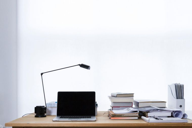 a desk holding research items including a laptop, books and a lamp