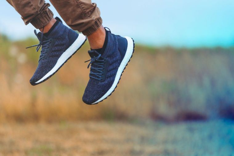 a person in a field wearing blue trainers jumping high off the ground
