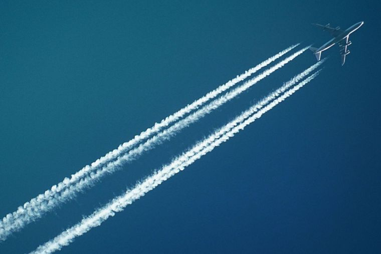 an aeroplane and its condensation trails in the sky seen from below