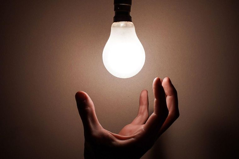 a hand reaching up to a bright lightbulb in a darkened room