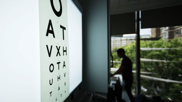 a darkened optician's room, lit by an eye test on a light box