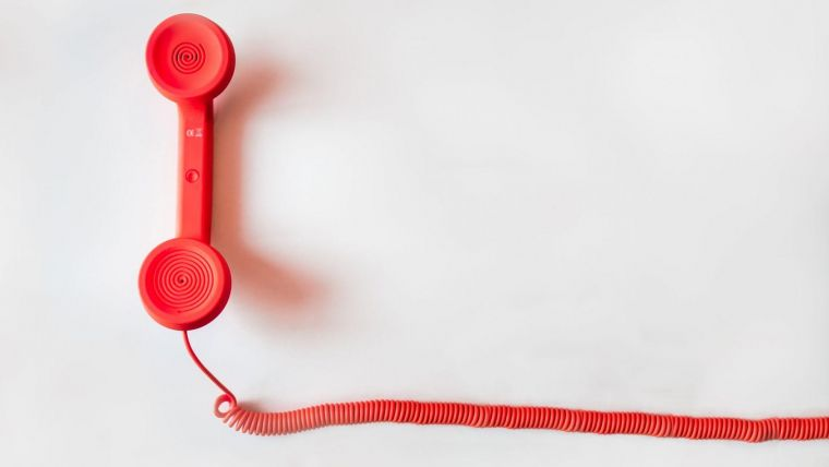 a red telephone handset with a long coiled chord