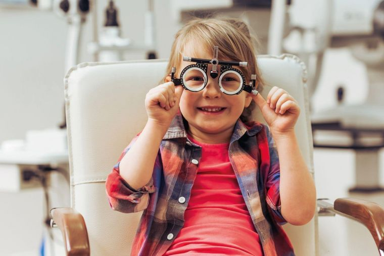 a boy playing with optician's glasses