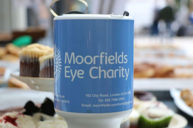 a Moorfields Eye Charity-branded collection cup sitting on a table full of cakes