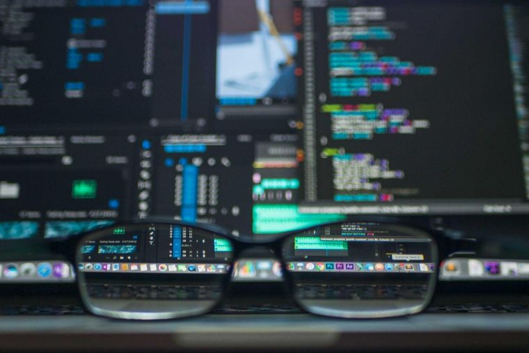 a pair of glasses on a surface, through which a screen with code is visible