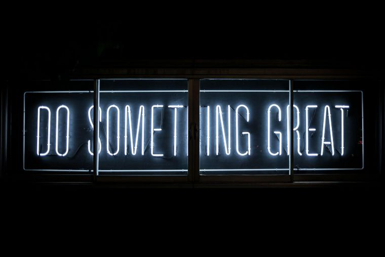 a neon sign reading do something great