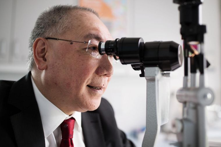 renown ophthalmic surgeon Prof Sir Peng Khaw looking through a microscope in a laboratory