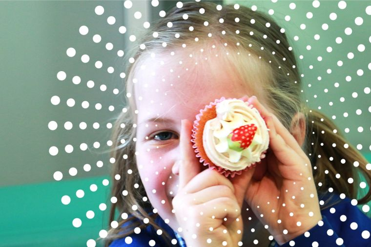 a young girl holding up a strawberry cupcake in front of her eye
