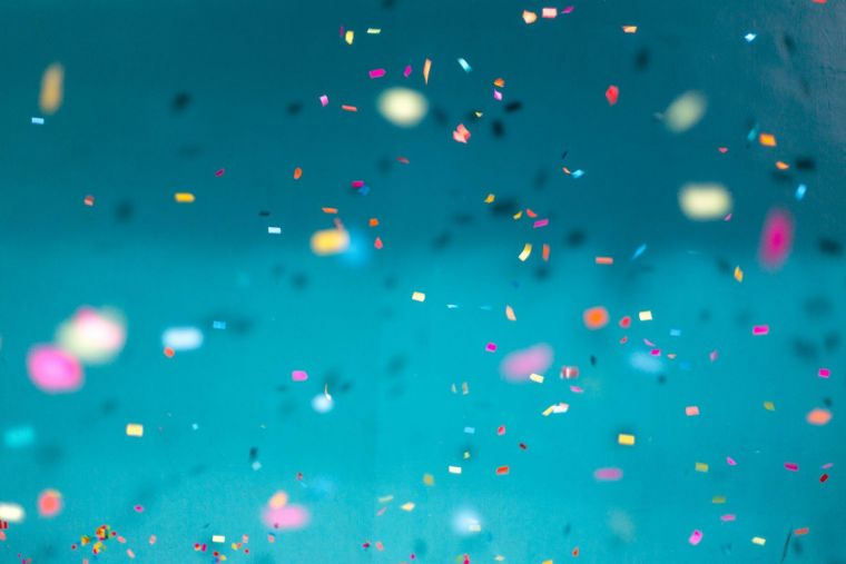 a close-up of multicoloured confetti falling in a blue room