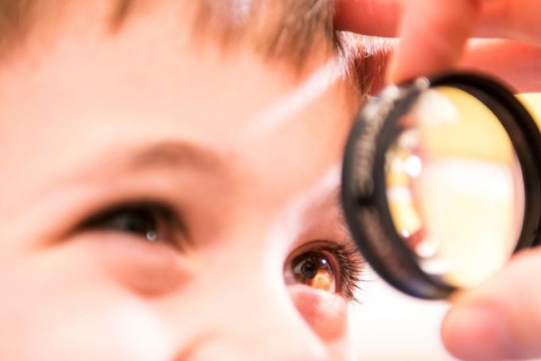 a smiling child having their eye examined with a magnifying glass