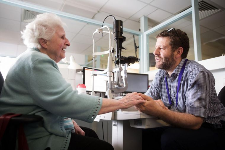 an elderly person smiling and speaking with an eye doctor