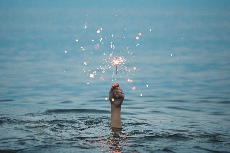 a hand emerging from a body of water holding a lit sparkler