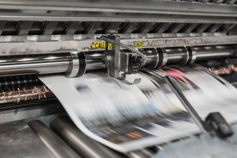 a close-up of a large printer producing newspapers