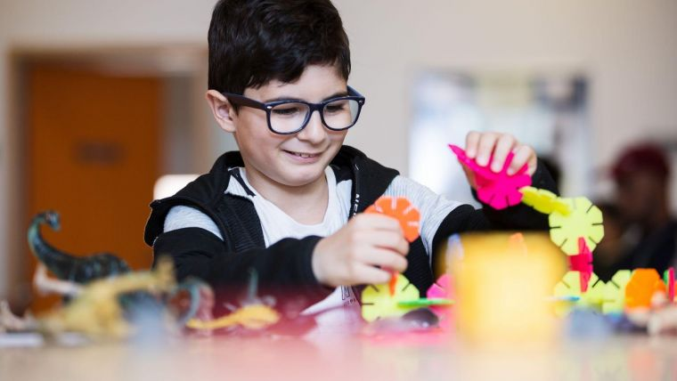 a happy young boy playing with colourful toys at a table