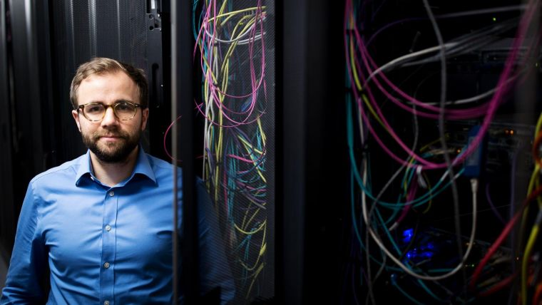 Dr Nikolas Pontikos, one of Moorfield Eye Charity's Career Development Award beneficiaries, standing beside an internet server with colourful wires