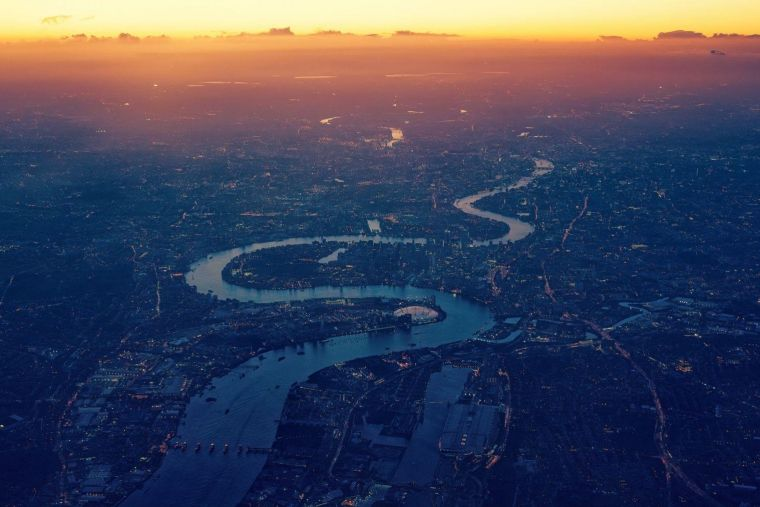 an ariel view of the thames winding its way inland as the sun sets on the horizon