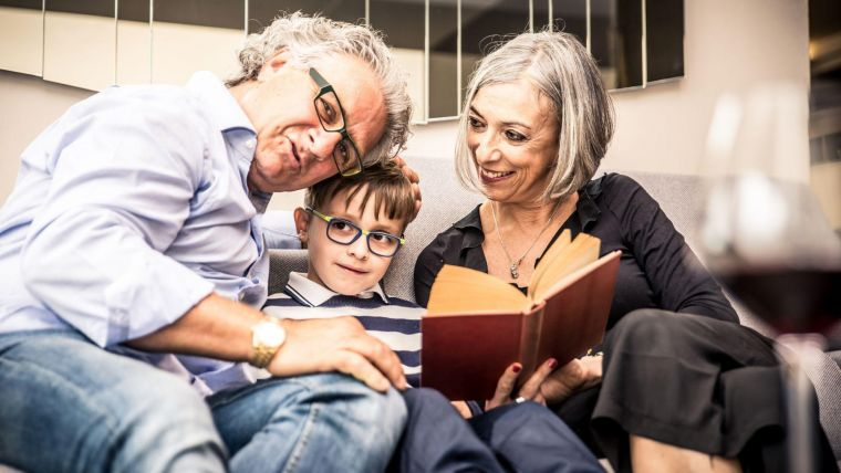 An older man and woman sitting on a sofa, with their grandson between them, all reading a book together. The grandfather and grandson are both wearing glasses.