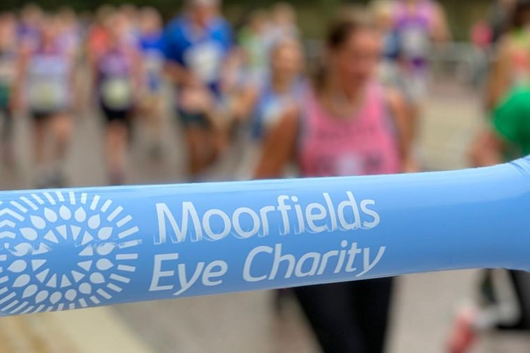 A blue Moorfields Eye Charity inflatable baton, with a large group of runners moving past in the background