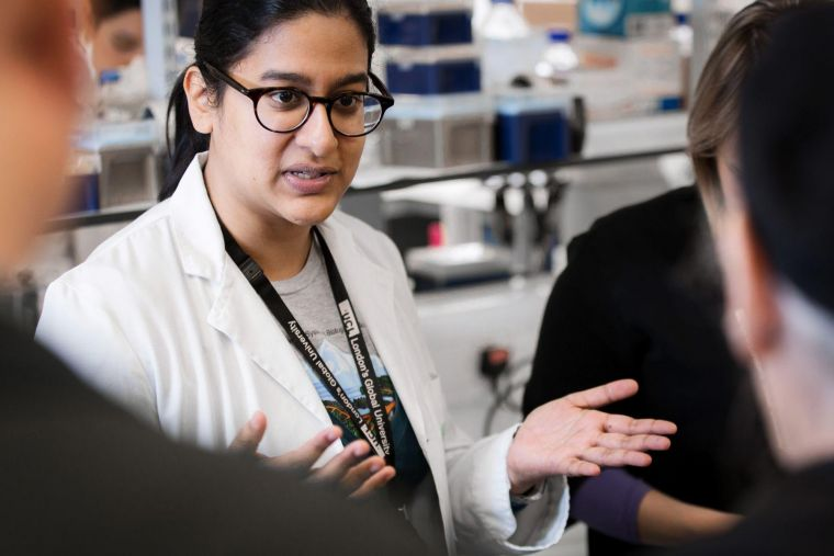 A female scientist in a white lab coat explaining something to a group in a laboratory.