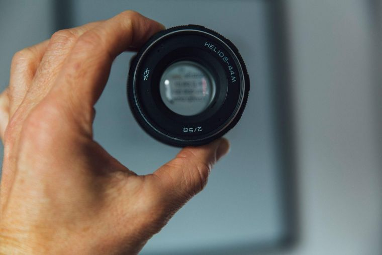 a single magnifying camera lens being held up by a hand
