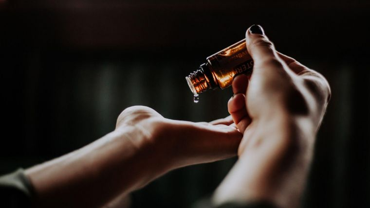 a person dispensing drops from a small, brown, medical bottle into the palm of their hand
