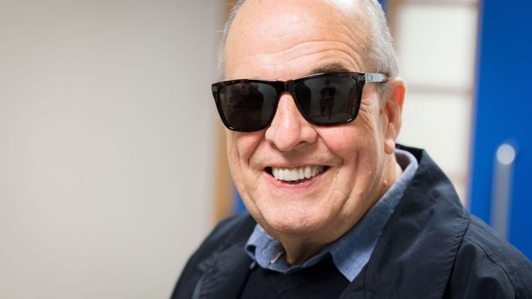 an elderly person wearing sunglasses and smiling at the camera