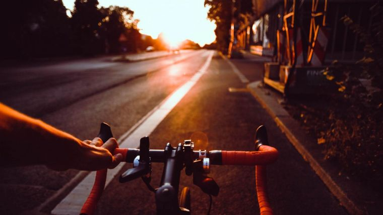a view of a road from the perspective of a cyclist looking over their handlebars and cycling towards a sunset