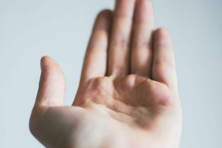 a close-up of an outstretched hand offering support to another person out of shot