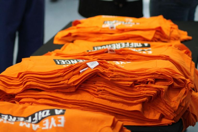 a number of piles of t-shirts for participants of the Eye to Eye walk