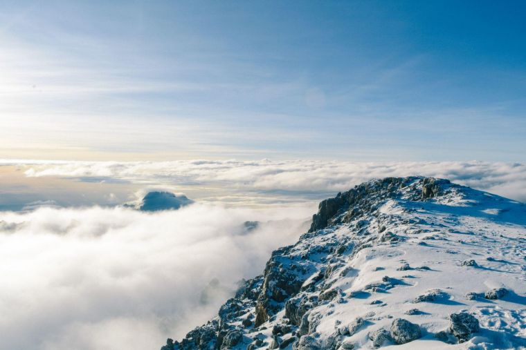 a view from the top of a snowy Mount Kilimanjaro, looking out over the clouds towards the horizon