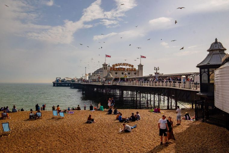 Brighton Pier on a clear, sunny day, with groups of people relaxing on the beach in front of it