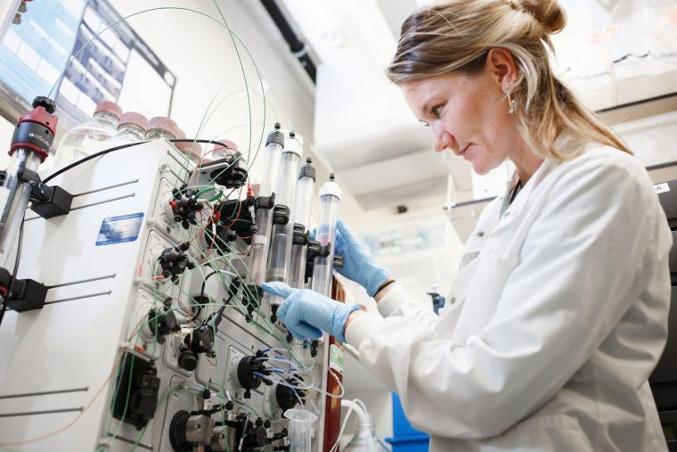 a researcher inspects samples in a laboratory machine