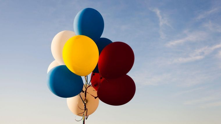 a bundle of yellow, blue, white and red balloons in front of a big, blue sky