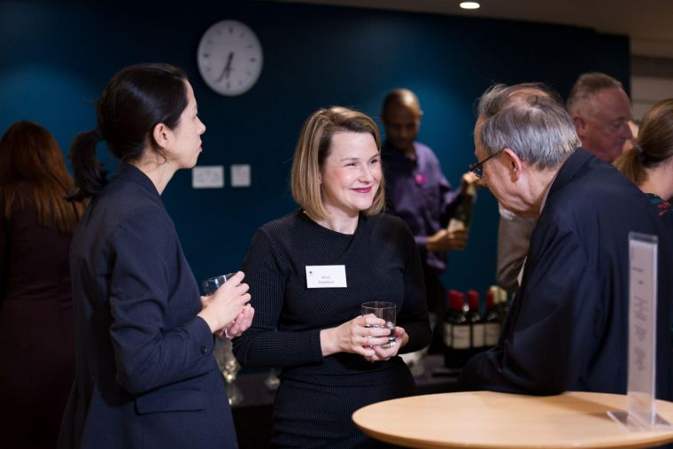 Dr Alice Davidson at a formal event, holding a drink and smiling in conversation with two people