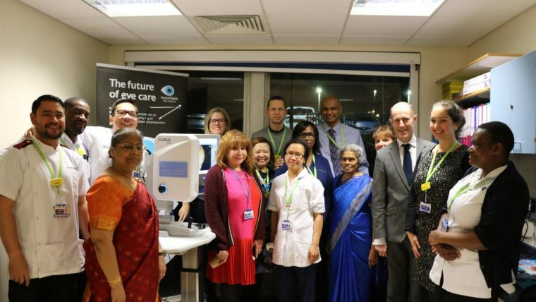 a large group of staff from, and supporters of, Moorfields in a testing room, celebrating the hospital's new ultra-wide field camera