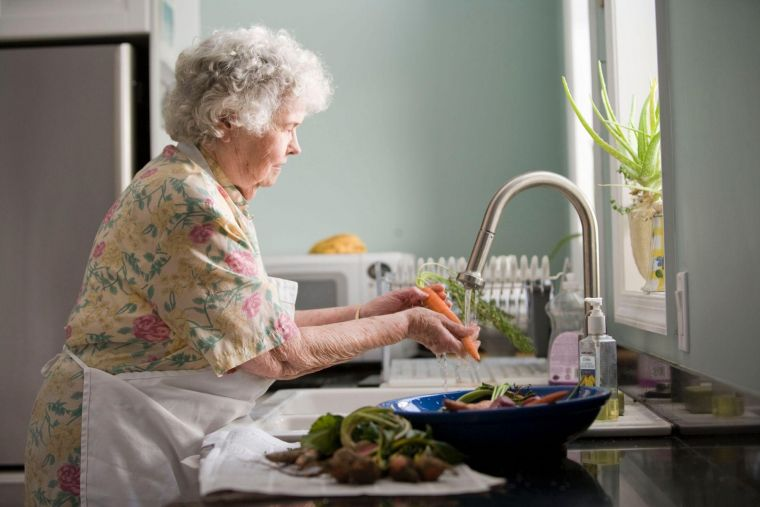 an elderly woman wearing an apron in a kitchen, washing carrots at a sink