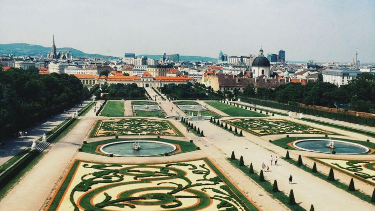 the large, elaborate, patterned gardens at Schönbrunn Palace in Vienna on a sunny day