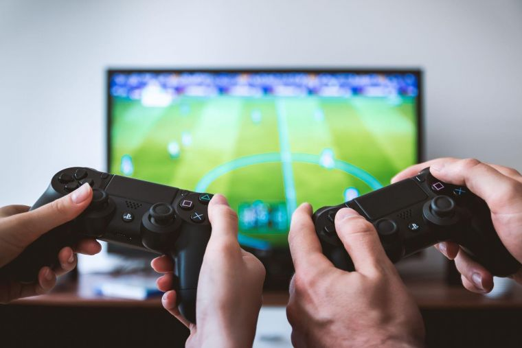 a close up of two people's hands and their controllers as they play on a games console, with the tv visible in the background