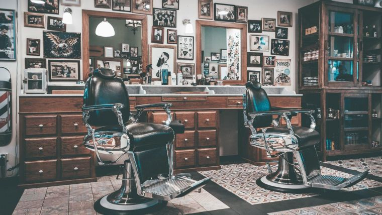 two empty barber shop chairs in an old-fashioned barber shop featuring walls filled with photo frames